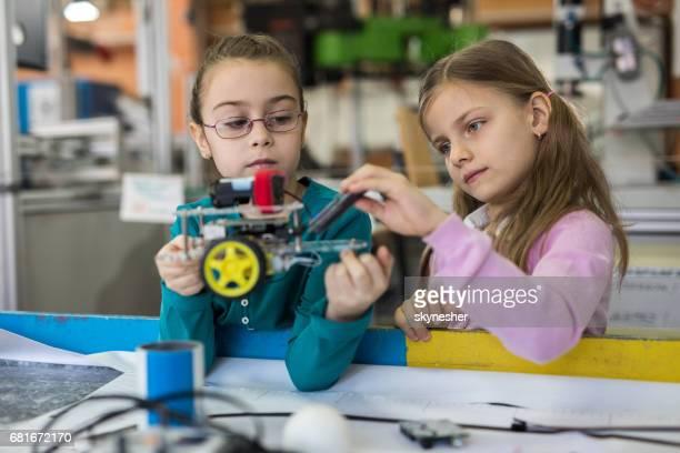 Kleine Mädchen, die Zusammenarbeit bei der Herstellung eines Roboters im Labor.