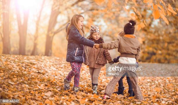 Small girls playing ring-around-the-rosy during autumn day in the park.