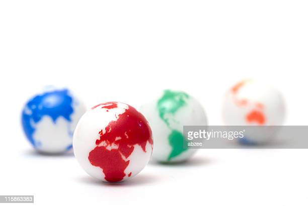 Small glass marbles with colorful globe artwork on white