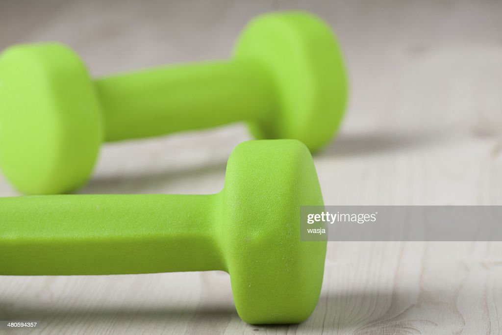 small green dumbbells on wooden surface : Stock Photo