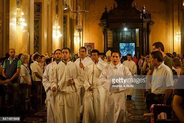 Small group of altar boys carrying a cross and censers walking inside the cathedral church of the city of Cordoba Argentina on the night of Easter...
