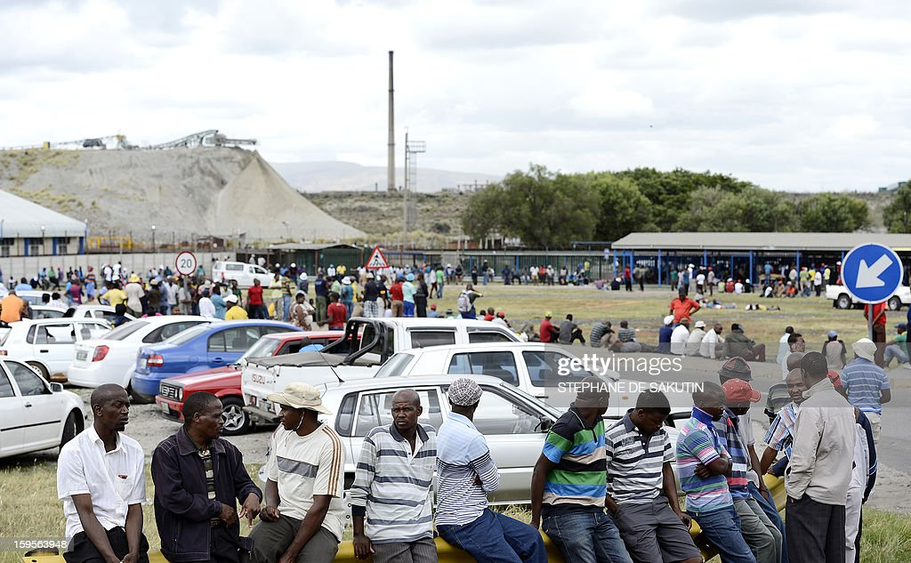 A small group of Anglo American Platinum workers downed tools and gather outside the Khomanani shaft, one of four the top global platinum producers, on January 16, 2013 in Rustenburg, northwest of Johannesburg. Amplats announced on January 15 it would close four shafts and sell a mine in sweeping restructuring, saying operations had become unsustainable. The vast majority of job cuts -- 13,000 in all -- would be made around Rustenburg. Last year's protests lead to the deaths of over 50 people, the majority strikers shot by police in one day of bloodshed at the Marikana platinum mine.