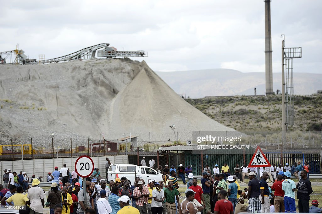 A small group of Anglo American Platinum workers who downed tools gather outside the Khomanani shaft, one of four the top global platinum producers, on January 16, 2013 in Rustenburg, northwest of Johannesburg. Amplats announced on January 15 it would close four shafts and sell a mine in sweeping restructuring, saying operations had become unsustainable. The vast majority of job cuts -- 13,000 in all -- would be made around Rustenburg. Last year's protests lead to the deaths of over 50 people, the majority strikers shot by police in one day of bloodshed at the Marikana platinum mine.