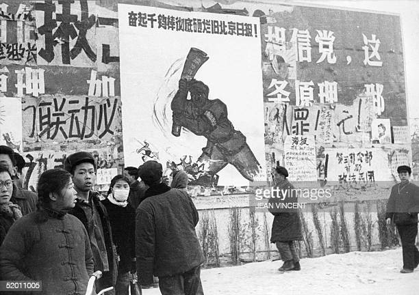 A small group of Chinese youths walk past several dazibaos the revolutionary placards in February 1967 in downtown Beijing during the 'Great...