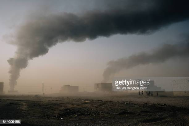 A small group of civilians walks carrying a white flag and few belongings to escape fighting between Islamic State militants and Iraqi security...