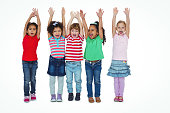 Small group of kids standing together with arms raised against a white background