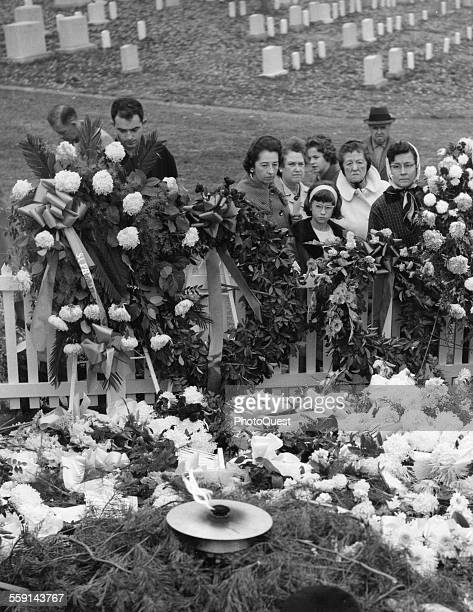 A small group of mourners stand beside the grave of assassinated President John F Kennedy at Arlington National Cemetery Washington DC November 25...