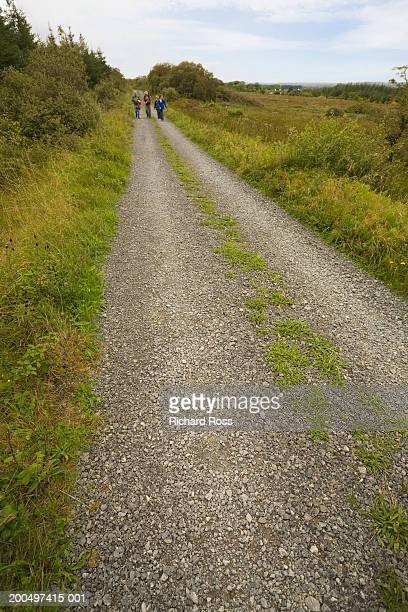 Small group of people hiking through rural landscape