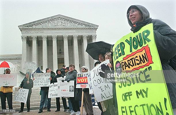 A small group of people protest outside of the US Supreme Court December 10 2000 in Washington DC The court will hear oral arguments from lawyers...
