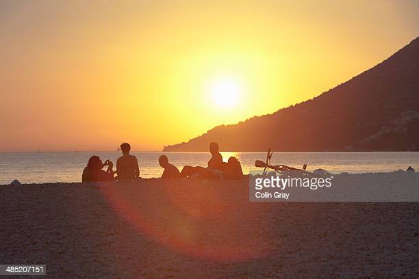 Small group of people watching sunset on beach, Vigan, Croatia