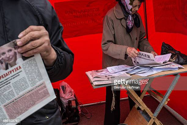 A small group of proRussian proCommunist and other individuals hand out party newspapers below a statue of Russian revolutionary leader Vladimir...