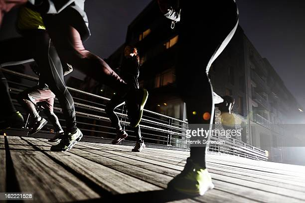 small group of runners on a bridge