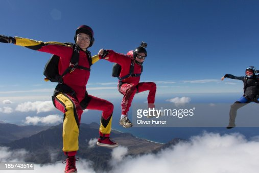 Small group of skydivers reaching to join hands
