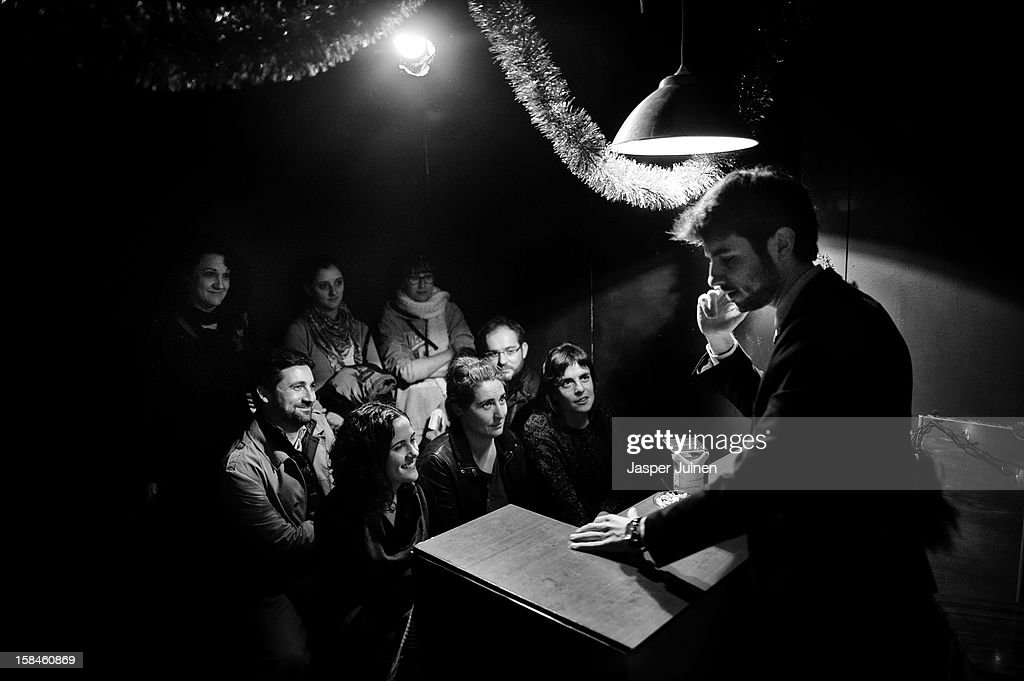 A small group of spectators watches as actor Hector Gonzalez Nieto performs during his 'Hacer el amor no solo es follar despacio' micro theater show at the 'Micro Teatro por Dinero' on December 15, 2012 in Madrid, Spain. In November 2009, fifty artists presented a theatre project in the thirteen rooms of a former brothel, two weeks before its demolition, with each function lasting less than 10 minutes. The initiative was a huge success, with more people queueing up outside than could enter. Today's 'Micro Theatre For Money' is named after the former brothel on Ballesta Street, and offers a cheap and original way for going out at night, especially in times of financial hardship. With each show priced at 4 Euros, over 150,000 spectators have already attended performances at the tiny theatre in the Malasana area. Anyone can submit a project to be chosen to perform for a month in one of the five tiny rooms in the basement of the theatre, making it an ideal platform for young Spanish authors and actors, often unemployed, to perform.