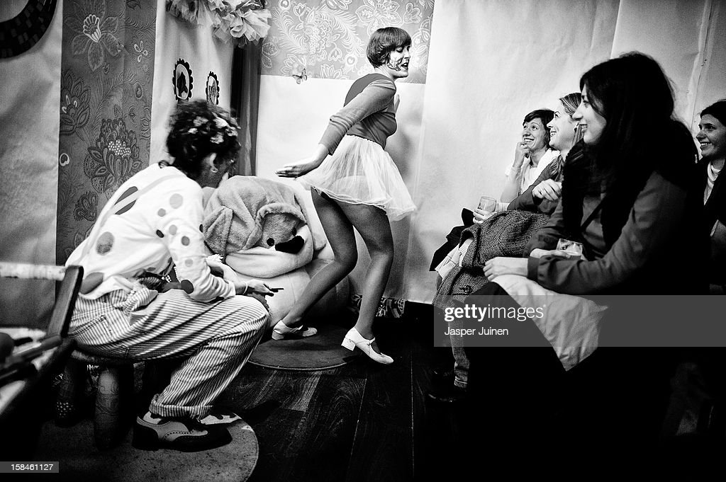 A small group of spectators watches as actress Aixa Villagran (L) performs with Eva Higueras during their 'Manual de orgasmos fingidos' micro theater show at the 'Micro Teatro por Dinero' on December 15, 2012 in Madrid, Spain. In November 2009, fifty artists presented a theatre project in the thirteen rooms of a former brothel, two weeks before its demolition, with each function lasting less than 10 minutes. The initiative was a huge success, with more people queueing up outside than could enter. Today's 'Micro Theatre For Money' is named after the former brothel on Ballesta Street, and offers a cheap and original way for going out at night, especially in times of financial hardship. With each show priced at 4 Euros, over 150,000 spectators have already attended performances at the tiny theatre in the Malasana area. Anyone can submit a project to be chosen to perform for a month in one of the five tiny rooms in the basement of the theatre, making it an ideal platform for young Spanish authors and actors, often unemployed, to perform.
