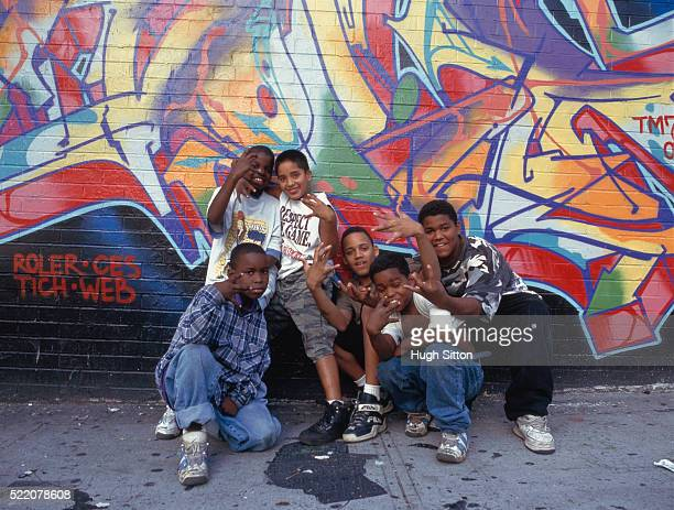 Small group of teenagers in front of graffiti on wall