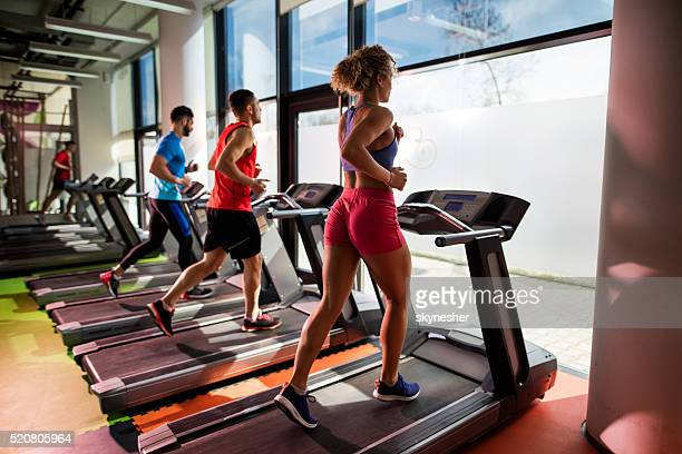 Small group of young people running on treadmill in gym.
