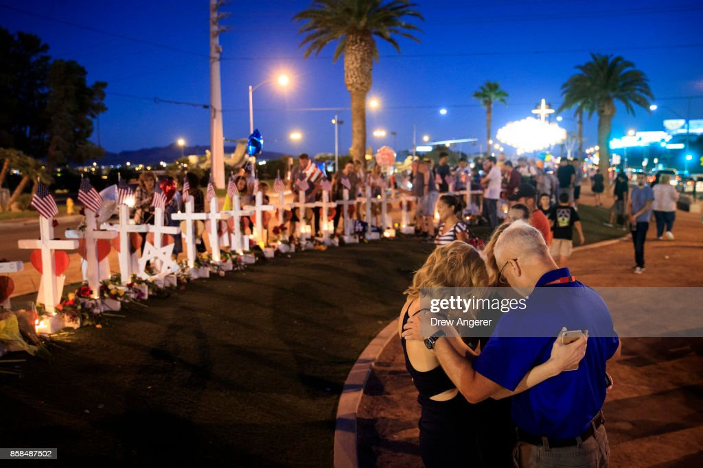 A small group prays at a makeshift memorial with 58 white crosses, one for each victim, on the south end of the Las Vegas Strip, October 6, 2017 in Las Vegas, Nevada. On October 1, Stephen Paddock opened fire on the crowd at the Route 91 Harvest country music festival, killing 58 people and injuring more than 450. The massacre is one of the deadliest mass shooting events in U.S. history.