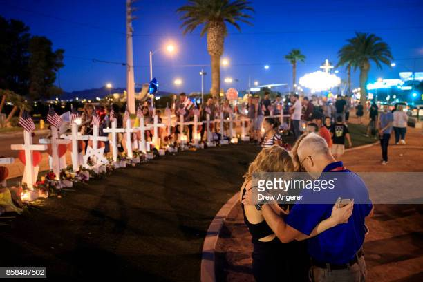 A small group prays at a makeshift memorial with 58 white crosses one for each victim on the south end of the Las Vegas Strip October 6 2017 in Las...