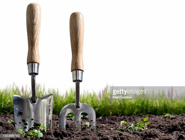 Small hand-held gardening trowel and fork stuck in some soil