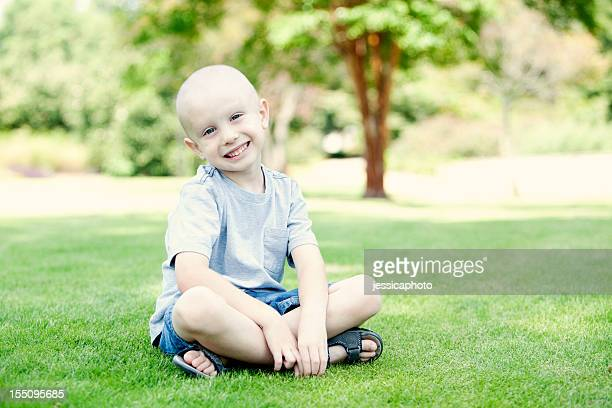 A small happy child sitting on the grass