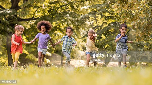Small happy kids having fun while running in nature.