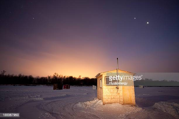 Small ice fishing huts at sunset