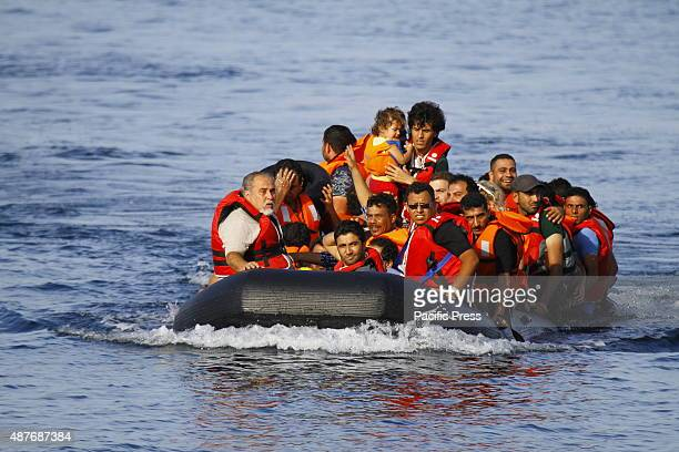 A small inflatable rubber dinghy loaded with refugees approaches the coast of Lesbos Hundreds of refugees mainly from Syria Iraq and Afghanistan are...
