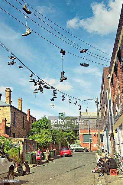 Small innercity street in Melbourne Australia with shoes suspended from power lines and young people socialising on the pavement