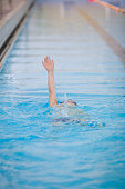 Small kid boy swims in a swimming pool - Back stroke style with whole body in the water. indoors. Sport activities at school. Competition in pool.