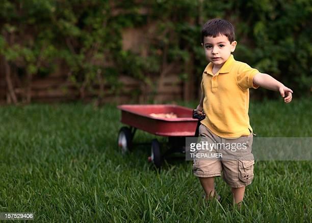 Petit enfant tirant un wagon rouge