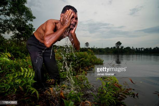 Small land owner Rahman washes his face in the sacred lake that they have preserved a new project for an ecoresort by the lake has been planned A...