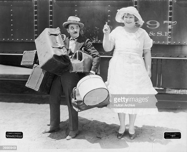 A small man carries several pieces of luggage while actress Babe London stands next to him wearing a white dress and hat in a still from the silent...
