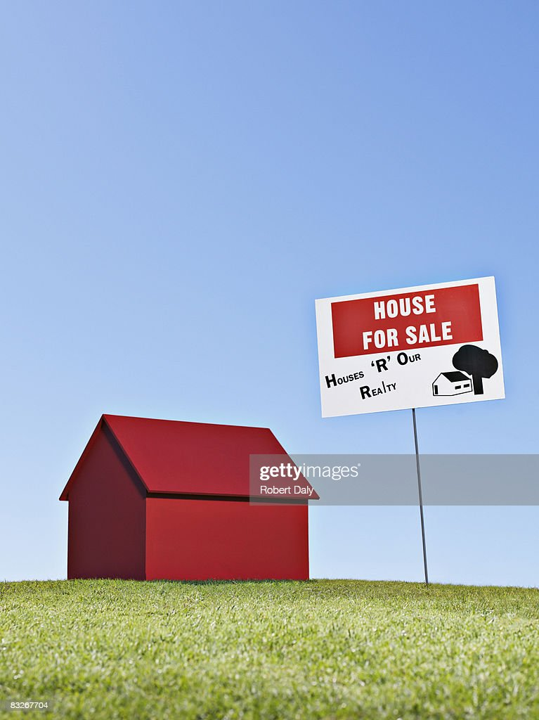 Small model house next to 'for sale' sign : Stock Photo
