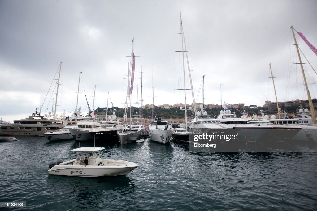 A small motor boat passes yachts moored in the harbor during the Monaco Yacht Show (MYS) in Monaco, France, on Thursday, Sept. 26, 2013. Over 100 of the world's luxury yachts will be displayed in Port Hercules during the 23rd MYS which runs from Sept. 25 - 28. Photographer: Balint Porneczi/Bloomberg via Getty Images