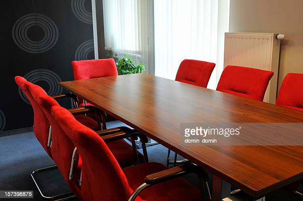 Small office interior with wooden desk, red comfortable armchairs, window