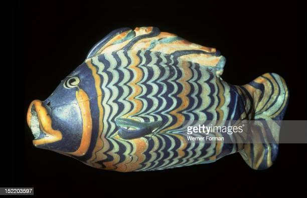 A small painted core glass unguent container in the form of a tilapia fish which was a symbol of rebirth Blue glass was modelled around the central...