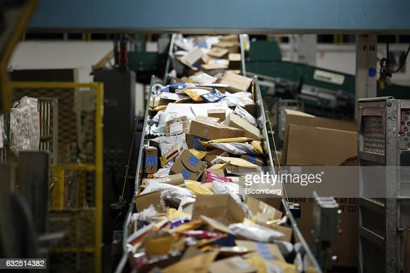 Small parcels move along a conveyor belt at the United States Postal Service sorting center in Louisville Kentucky US on Friday Jan 13 2017 Starting...