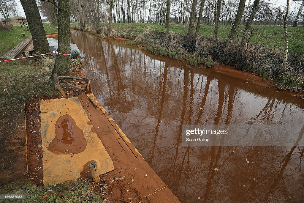 A small pier used by a local tour operator for launching flat-bed canoes stands covered in mud tinted orange due to a high content of iron sediment at the Wudritz creek in the Spreewald region on April 17, 2013 near Luebbenau, Germany. The Wudritz is heavily burdened with iron from the nearby former Schlabendorf open pit coal mine, which has since been turned into a lake called the Schlabendorfer See. Many creeks and small rivers that feed the Spree River have turned a rich orange or brown, sometimes even red, due to the sediments flowing from several former open pit coal mines. The Spreewald is a popular tourist destination known for its network of canals and local tour operators fear the sediment will turn the waters there orange as well, which could seriously impact the tourist seasons. Though the iron sediment is not poisonous, some local farmers claim they have been forced to filter the water they use to irrigate their fields, and many people report the disappearance of fish and other fauna.