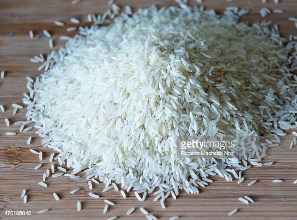 Small pile of long grain white rice over a wooden surface with natural illumination showing highlights and shadows basmati rice in cutting board
