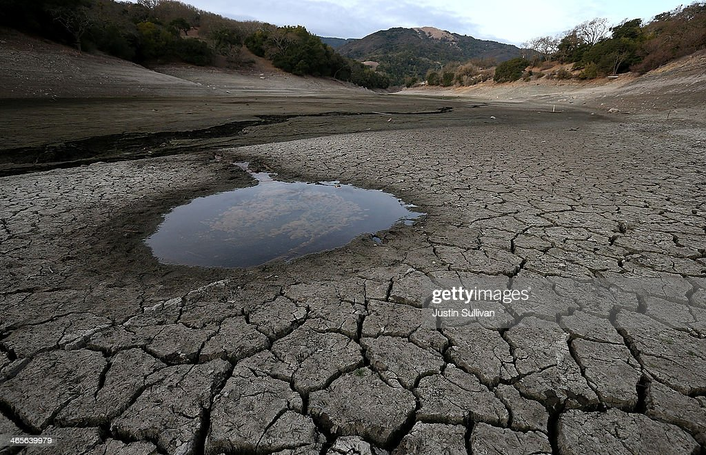 A small pool of water is surrounded by dried and cracked earth that was the bottom of the Almaden Reservoir on January 28 2014 in San Jose California...
