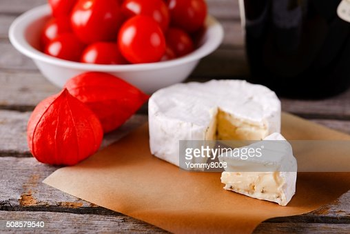 Small portion of camembert cheese in front of the rest : Stock Photo
