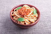Small portion of cooked spaghetti with tomato relish and basil leaves in a brown small wooden bowl closeup
