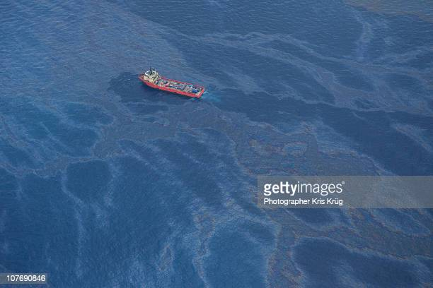 A small red boat floats in an oily gulf of Mexico