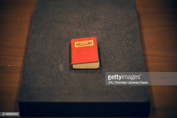 Small red book with gold font on the front cover on a black platform on a wooden table 2016