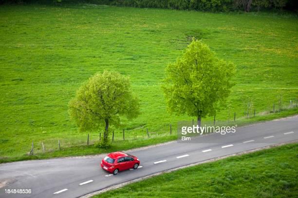 Kleines rotes Auto fahren auf ländliche Straße schnell