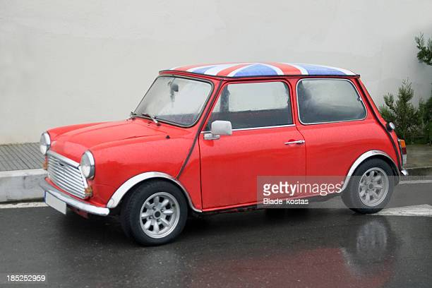 A small, red classic car with an English flag on top