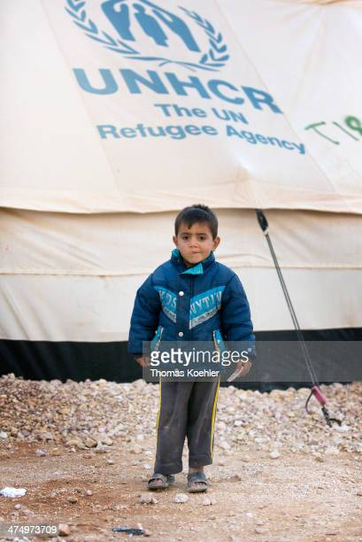 A small refugee boy in front of a tent featuring the UNHCR logo pitched at the Zaatari refugee camp where around 160000 Syrian refugees are living at...