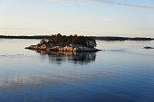 Small rocky island in archipelago of Turku, Finland in sea at sunset