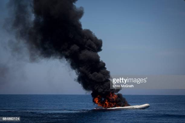 A small rubber boat used by refugees and migrants is seen burning after being set alight after all people were rescued by rescue crews from the...